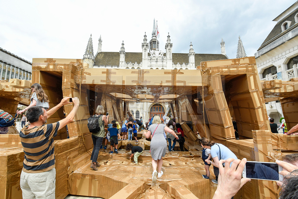 © Licensed to London News Pictures. 21/07/2019. LONDON, UK.  Members of the public tear apart The People's Tower, a monumental cardboard structure, built by artist Olivier Grossetête aided by a local volunteers, which stood in Guildhall Yard.  Over 1,000 boxes were used to build the 20m high artwork, inspired by the Guildhall building.  The four day construction process culminates in the structure being ceremonially torn down.  Photo credit: Stephen Chung/LNP