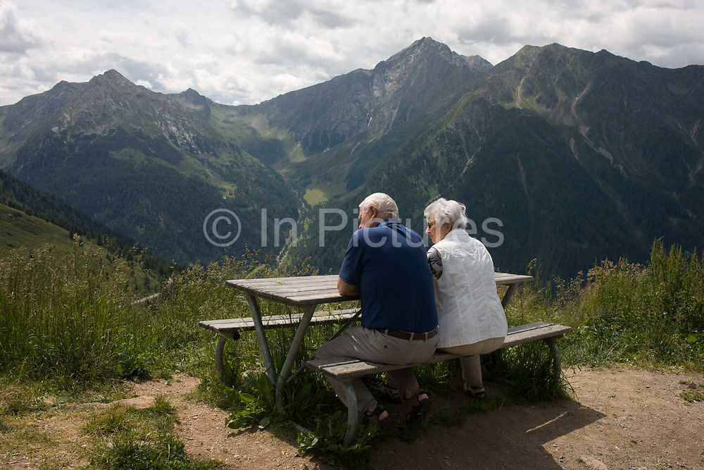 Elderly visitors admire the views from the roadside near the top of the Jaufenpass, the highest point at 2,094 metres on the road between Meran-merano and Sterzing-Vipiteno in South Tyrol, Italy. South Tyrol has a surface area of 7,400sq km, roughly the same as the Black Forest and is the largest province in Italy with 60% of this is 1,600 metres above sea level and its birth rate is the fourth highest of Italian provinces. With just half a million inhabitants, it attracts nearly 6m holidaymakers annually. The Jaufenpass (Italian: Passo di Monte Giovo) (alt 2094m.) is a high mountain pass in the Alps in the South Tyrol in Italy. It connects Meran and Sterzing on the road to the Brenner Pass. It is the northernmost pass in the Alps that is completely in Italy. The pass road is very winding, with many switchbacks.