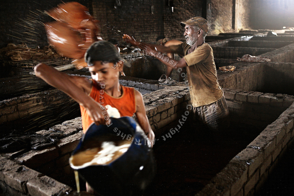 An elder and a young boy are using their bare hands to collect skins from a bath of contaminated water during the process of liming, removing hair and impurities with the use of various agents, in an illegal tannery unit located within the industrial area of Jajmau, Kanpur, Uttar Pradesh.