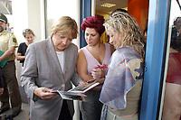 22 JUL 2003, FREITAL/GERMANY:<br /> Angela Merkel, CDU Bundesvorsitzende und CDU/CSU Fraktionsvorsitzende, sieht sich Fotos des Hochwassers an, waehrend dem Gespraech mit einer Friseurin (M) und ihrer Kundin (R), waehrend dem Besuch der seinerzeit von der Hochwasserkatastrophe 2002 stark betroffene Stadt Freital<br /> IMAGE: 20030722-01-049<br /> KEYWORDS: Bueger, Bürger, Gespräch
