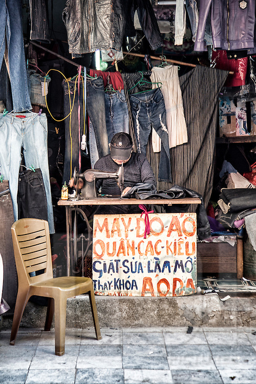 A worker sews a garment in a leather shop along Hang Trung 'leather street' in Hanoi's Old Quarter, Vietnam, Southeast Asia