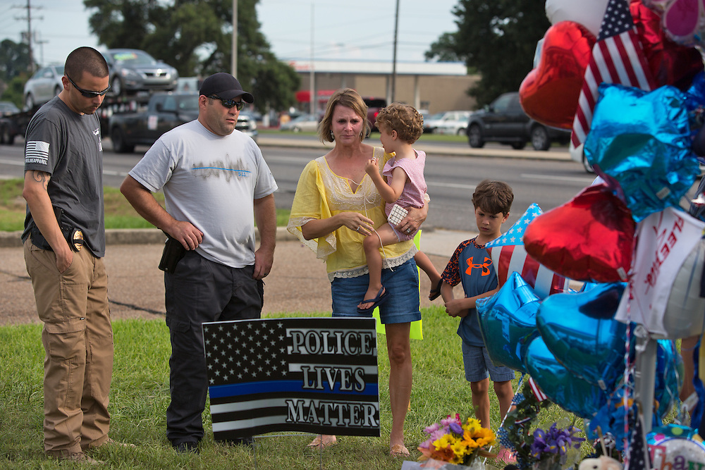 Glynes Hyde with her son Eric at a makeshift memorial in Baton Rouge in front of B-Quik gas station for the police officers killed by a lone gunman, that continues to grow.  She can't believe this happened in Baton Rouge, where she was born and raised and isn't surprised someone from out side the area killed the police officers. She doesn't think racism is a big problem in Baton Rouge, she thinks poverty is.