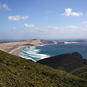Cape Reinga at the north western most tip of the Aupouri Peninsula, at the northern end of the North Island of New Zealand. . Cape Reinga is  a favourite tourist attraction and the meeting point  between the Tasman Sea to the west and the Pacific Ocean to the east. From the lighthouse it is possible to watch the tidal race, as the two seas clash to create unsettled waters just off the coast. Cape Reinga, North Island, New Zealand, 21st November 2010. Photo Tim Clayton.