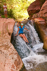 USA Utah, hike up the slot canyon known as Kanarra Creek, near Zion National Park, showing the red iron oxide rocks and the water stream erosion creating magnificent scenery.