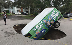"""Residents of the Astor Park apartment complex off Tuskawilla Road in Winter Springs, FL, USA were shocked to find a van head first in a sinkhole in the parking lot. The driver apparently crawled out by kicking out the back window of the vehicle. """"It's very strange and very scary,"""" resident Mario Lopez said. Photo by Joe Burbank/Orlando Sentinel/TNS/ABACAPRESS.COM"""