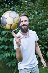 Young man balancing football on finger, Bavaria, Germany