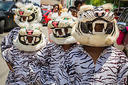 """05 JULY 2014 - BANGKOK, THAILAND: Children in tiger outfits march in a parade for vassa in Bangkok. Vassa, called """"phansa"""" in Thai, marks the beginning of the three months long Buddhist rains retreat when monks and novices stay in the temple for periods of intense meditation. Vassa officially starts July 11 but temples across Bangkok are holding events to mark the holiday all week.    PHOTO BY JACK KURTZ"""