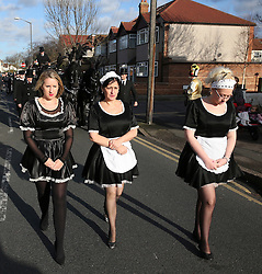 © Licensed to London News Pictures. 09/12/2015. London, UK. Three women dressed in maids uniforms lead the funeral procession a a carriage carrying the coffin travels to the service. The funeral of former brothel keeper Cynthia Payne takes place at the South London Crematorium.  In 1980 Cynthia Payne was sentenced to 18 months for running a brothel at her house on Ambleside Avenue in Streatham. It was alleged, at the time, that judges and Members of Parliament were visitors to her establishment. Photo credit: Peter Macdiarmid/LNP