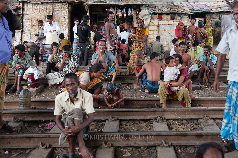 Life in the slums by the  railway tracks in Tejgaon.People sheltering from the rain under the over pass. Centre for Services and Information on Disability (CSID) is a charity working for intergrating disabled children into mainstream society. CSID provide help to several children and their families living  in the informal settlent bvy the tracks.