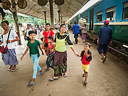 26 OCTOBER 2015 - YANGON, MYANMAR:  People walk through Yangon Central Railroad Station after arriving in Yangon on the Circular Train. The Yangon Circular Railway is the local commuter rail network that serves the Yangon metropolitan area. Operated by Myanmar Railways, the 45.9-kilometre (28.5mi) 39-station loop system connects satellite towns and suburban areas to the city. The railway has about 200 coaches, runs 20 times daily and sells 100,000 to 150,000 tickets daily. The loop, which takes about three hours to complete, is a popular for tourists to see a cross section of life in Yangon. The trains run from 3:45 am to 10:15 pm daily. The cost of a ticket for a distance of 15 miles is ten kyats (~nine US cents), and for over 15 miles is twenty kyats (~18 US cents).    PHOTO BY JACK KURTZ