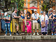 16 JULY 2016 - UBUD, BALI, INDONESIA: Tourists line the main street in Ubud before the procession for the mass cremation. Local people in Ubud exhumed the remains of family members and burned their remains in a mass cremation ceremony Wednesday. Almost 100 people were cremated and laid to rest in the largest mass cremation in Bali in years this week. Most of the people on Bali are Hindus. Traditional cremations in Bali are very expensive, so communities usually hold one mass cremation approximately every five years. The cremation in Ubud concluded Saturday, with a large community ceremony.      PHOTO BY JACK KURTZ