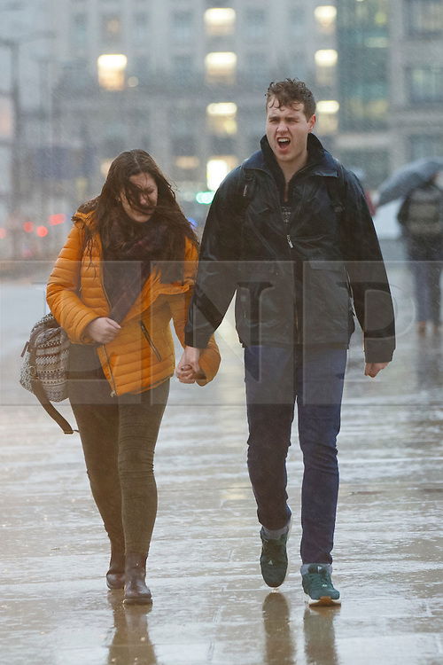 © Licensed to London News Pictures. 07/01/2016. London, UK. A couple walking during a heavy rain on London Bridge in London on Thursday, 7 January 2016. Photo credit: Tolga Akmen/LNP