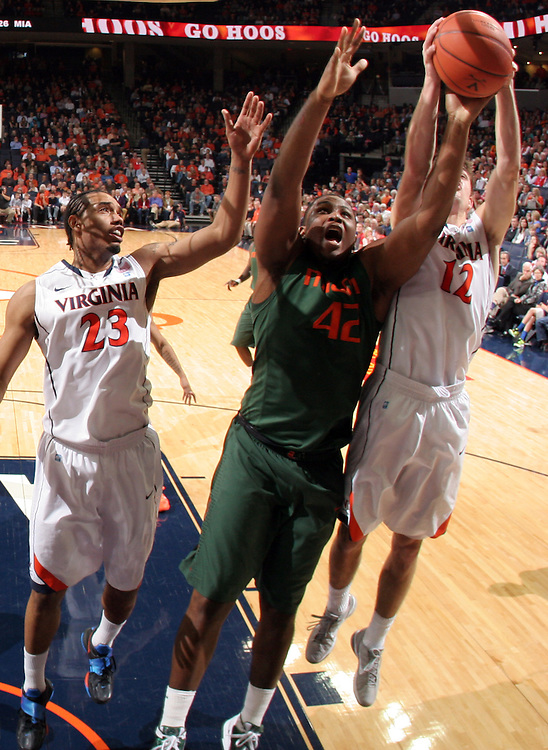 CHARLOTTESVILLE, VA- JANUARY 7: Reggie Johnson #42 of the Miami Hurricanes reaches for the rebound next to Mike Scott #23 and Joe Harris #12 of the Virginia Cavaliers during the game on January 7, 2012 at the John Paul Jones Arena in Charlottesville, Virginia. Virginia defeated Miami 52-51. (Photo by Andrew Shurtleff/Getty Images) *** Local Caption *** Joe Harris;Mike Scott;Reggie Johnson