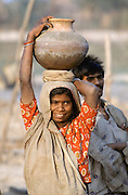 Indian woman carrying water pot on her head, India