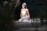 bride in modern wedding gown sitting on abandoned driveway