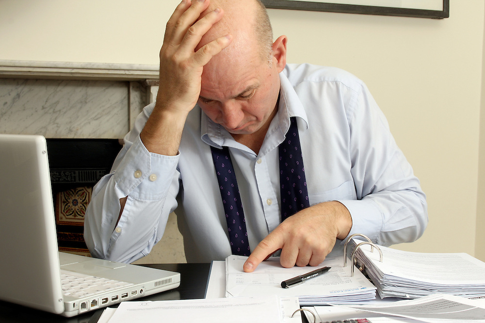 Middle aged man looking worried as he checks his bank finances.