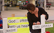 Woman writes a message on a cross at a makeshift memorial where six officers were shot on Airline Highway in Baton Rouge. Three of the officers were killed and another one remains in criticial condition. The memorial in from of the  B-Quik gas station  continues to grow.