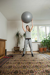 Young woman doing exercise with fitness ball in living room, Munich, Bavaria, Germany