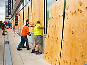 31 MAY 2020 - DES MOINES, IOWA: Workers from Hy-Vee Construction put plywood over shattered windows at the Hy-Vee grocery store in downtown Des Moines. The windows were shattered by rioters early Sunday morning. A group of rioters, protesting the death of George Floyd in police custody in Minneapolis, smashed windows in businesses and restaurants around the Polk County Courthouse in Des Moines. Des Moines police said they made 25 arrests Saturday night and very early Sunday morning. No one was hurt in the disturbances.       PHOTO BY JACK KURTZ