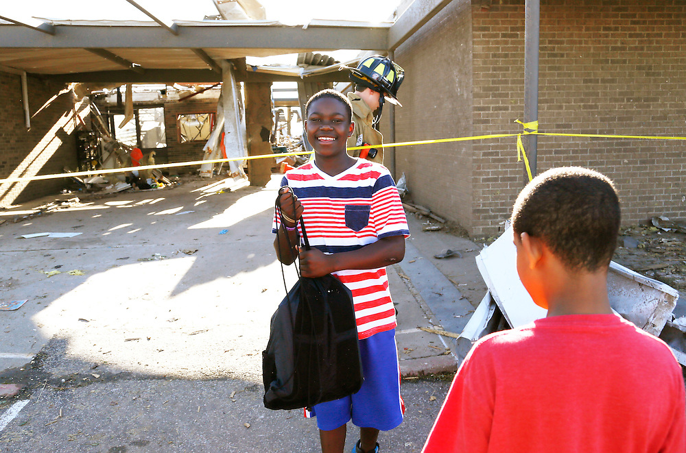 Jordan Humphrey, 6th grader at tornado-damaged Briarwood elementary school smiles after his backpack was retreived for him by a firefighter (rear) in Oklahoma City, Oklahoma May 22, 2013.  No students were killed at this school. Rescue workers with sniffer dogs picked through the ruins on Wednesday to ensure no survivors remained buried after a deadly tornado left thousands homeless and trying to salvage what was left of their belongings.  REUTERS/Rick Wilking (UNITED STATES)