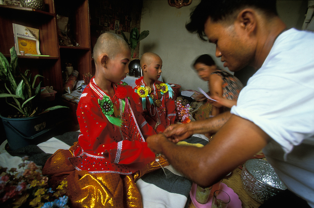 Relatives tie strings for good luck and give a monetary gift to two young cousins at Poy Sang Long, the yearly ordination of novice monks, Mae Hong Son, Thailand.