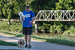 Dog-walker on the Trinity Trails near the Trinity River and train trestle, Fort Worth, Texas, USA.