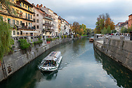 Ljubljana, Slovenia - October 20, 2013: A tour boat gives tourists a view of the autumn cityscape on the  Ljubljanica River in Ljubljana, Slovenia.