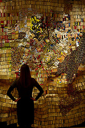© Licensed to London News Pictures. 21/05/2012 London, UK. A Bonhams staff member with a hanging tapestry titled 'New World Map' by Ghana's El Anatsui. The 11ft  by 16ft work goes to auction next week as part of the Modern and Contemporary African Art sale and is expected to fetch between £500,000 to £800,000..Photo credit : Simon Jacobs/LNP