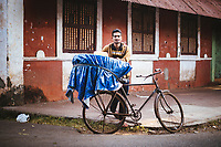 A portrait of a young man selling bread from a bicycle in Panjim, India.