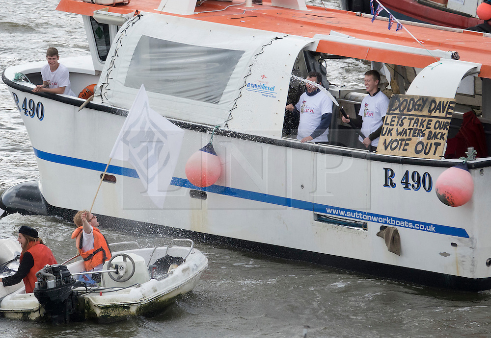 © Licensed to London News Pictures. 15/06/2016. London, UK.  Crew members on board a vote leave boat squirt water from a hose on 'In' campaigners as in and out flotillas converge on the Thames near Parliament. Photo credit: Peter Macdiarmid/LNP