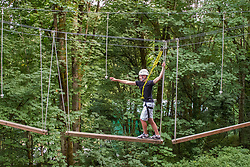 United States, Bellevue, teenage boy crossing plank bridge at Discovery Challenge Ropes Course.  MR