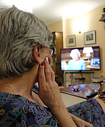 Caroline Hogan, 65, watches a pre-recorded speech by Queen Elizabeth II on television in London, to mark the 75th anniversary of VE Day.