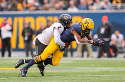 Nov 23, 2019; Morgantown, WV, USA; West Virginia Mountaineers wide receiver T.J. Simmons (1) catches a pass and is tackled by Oklahoma State Cowboys safety Tanner McCalister (2) during the third quarter at Mountaineer Field at Milan Puskar Stadium. Mandatory Credit: Ben Queen-USA TODAY Sports