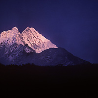 Mist wreathes Mount Thamserku at sunset, view from Khumjung.