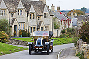 Vintage car drives through Windrush village on a Veteran Car Club rally day, Gloucestershire, United Kingdom