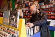 A man searching through vinyl records at Honest Jon's Records on the 26th March 2018  in Notting Hill, West London in the United Kingdom.