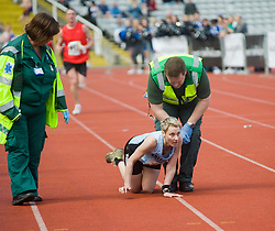 As Paramedics move into help exhausted runner they are told by Race officials not to touch Deborah Richards of Sheffield Running Club as she struggles to finish the Sheffield Half Marathon. Deborah collapsed after staggering in to Don Valley Stadium before beginning to crawl for the finish line <br /> <br /> 25 April 2010. <br /> Images © Paul David Drabble Within site of the finish line and surrounded by paramedics and race officials Deborah Richards of Sheffield Running Club fights to make the finish line in the Sheffield Half Marathon