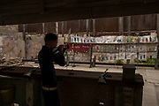 A man at a small improvised amusement park fires on bottles, Cuba.