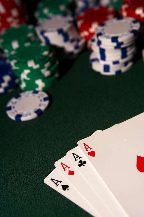 Playing cards showing four aces with out of focus poker chips on green felt table