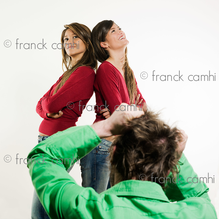 studio shot pictures on isolated background of two sisters twin women friends in front of a man tearing his hair away