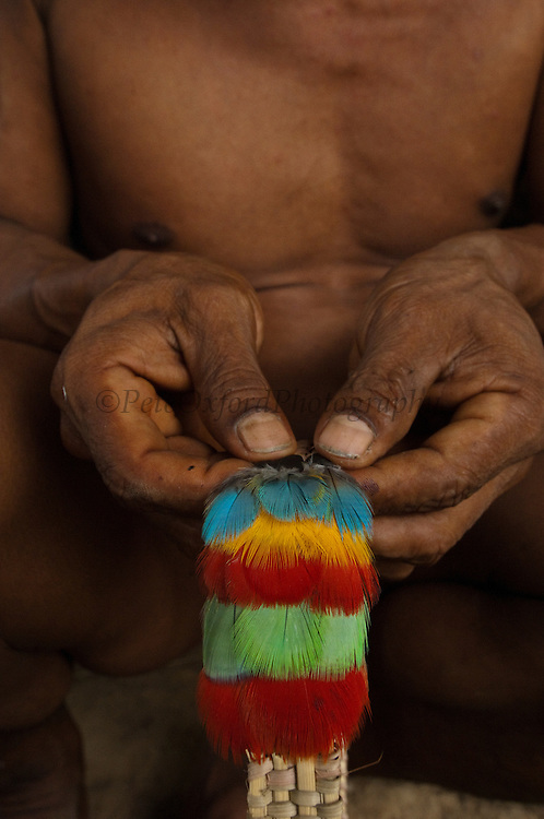 Huaorani Indian feather crown being made. Gabaro Community. Yasuni National Park. Amazon rainforest, ECUADOR.  South America<br /> First a basket-like weave fibre ring is made. Then feathers collected from hunted toucans, parrots, macaws and other colourful birds are stuck on with heated beeswax. Macaw tail feathers - standing up are sometimes added later.<br /> This Indian tribe were basically uncontacted until 1956 when missionaries from the Summer Institute of Linguistics made contact with them. However there are still some groups from the tribe that remain uncontacted.  They are known as the Tagaeri. Traditionally these Indians were very hostile and killed many people who tried to enter into their territory. Their territory is in the Yasuni National Park which is now also being exploited for oil.