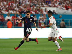 March 23, 2018 - Miami Gardens, Florida, USA - Croatia forward Nikola Kalinic (16) and Peru midfielder Anderson Santamaria (4) chase a ball during a FIFA World Cup 2018 preparation match between the Peru National Soccer Team and the Croatia National Soccer Team at the Hard Rock Stadium in Miami Gardens, Florida. (Credit Image: © Mario Houben via ZUMA Wire)