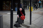 Man with a red hat and scarf stoops to access a small case in a central London street.