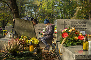 Father and daughter clean up a grave and put candles and flowers on it in Rakowicki cemetery in Krakow, Poland 2019.