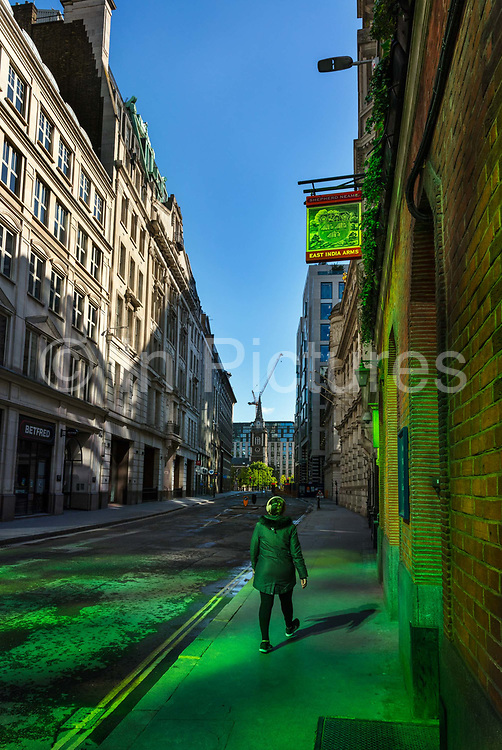 Walker passing the East India Arms pub in the City of London during the coronavirus pandemic on the 2nd May 2020 in London, United Kingdom. The building is located on Fenchurch Street next to the place where the East India Company had its headquarters. The 1829 building is now the oldest building in the Lloyds Avenue Conservation Area.