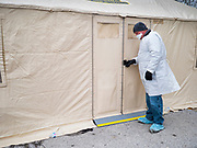"""16 MARCH 2020 - DES MOINES, IOWA: A public health employee in protective clothing at the health screening tent on the east side of the Iowa State Capitol in Des Moines. Because of numerous reports of Coronavirus in Iowa, the governor is suspending the legislative session for 30 days. It was scheduled to run until mid-April. Sunday night, the Governor announced that the state health department had recorded """"community spread"""" in Des Moines. As a result the State Capitol instituted mitigation measures that included mandatory health screening for everyone going into the building, canceling group tours of the building, and closing the souvenir shop and snack bar.     PHOTO BY JACK KURTZ"""