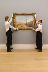 Sotheby's London, November 28th 2014.Sotheby's hold a preview for their December 3rd sale of Old Master and British Paintings at their Bond Street gallery. The exhibition runs from November 29th to December 3rd. PICTURED: Sotheby's gallery technicians hang Canaletto's Venice, the Piazza San Marco Looking East Towards the Basillico, which is expected to fetch up to £7 million at auction.