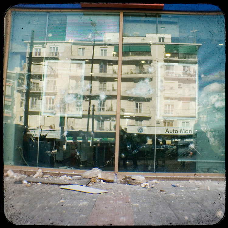 The shuttered windows of Eurobank - bank brunch in Alexandras street.<br />  <br /> The killing of the 15 year old boy Alexandros Grigoropoulos by a policeman resulted in widespread riots that altered the city landscape. When I walked in the streets of my town the day after the riots I instantly forgot the image I had about Athens, that of a bustling, peaceful, energetic metropolis and in my mind came the old photographs from WWII, the civil war and the students uprising against the dictatorship. Thus I decided not to turn my digital camera straight to the destroyed buildings but to photograph through an old camera that worked as a filter, a barrier between me and the city.