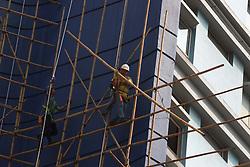 October 10, 2018 - Hong Kong, CHINA - A worker carrying a bamboo on the scaffolding outside the hotel awaiting to be demolished. Hong Kong is where Chinese traditional art of bamboo scaffolding is being kept as a classic architectural craft.Oct-10,2018 Hong Kong.ZUMA/Liau Chung-ren (Credit Image: © Liau Chung-ren/ZUMA Wire)