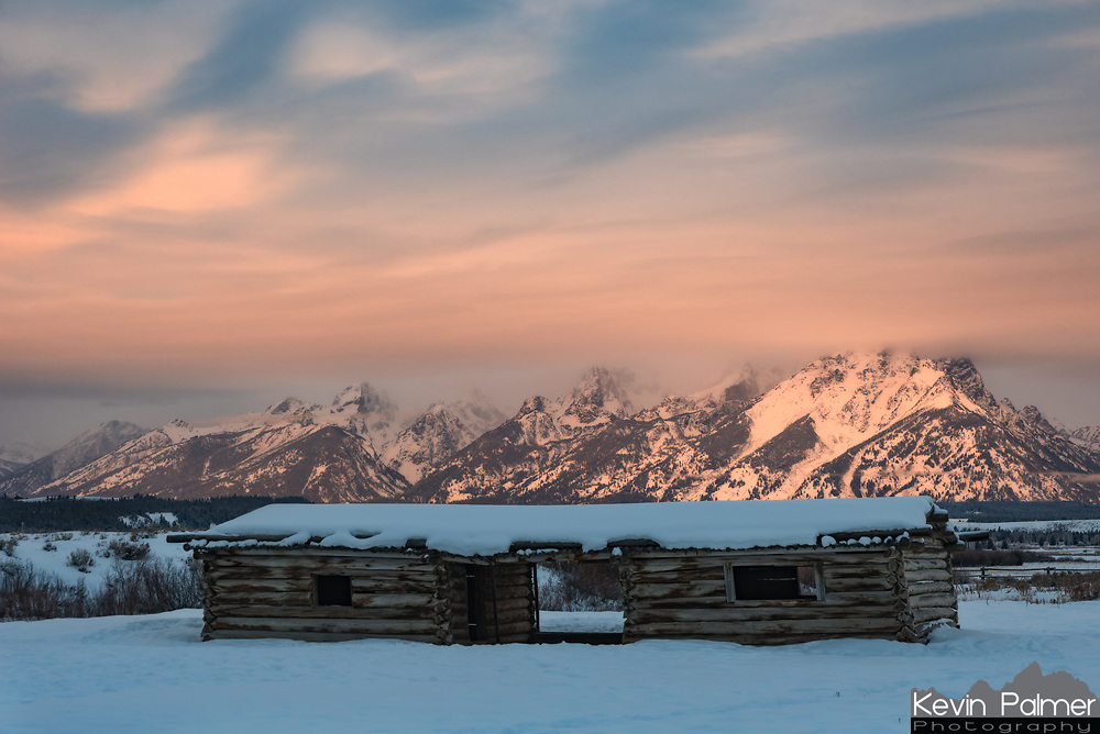 Low clouds above the Tetons light up at sunrise over Cunningham Cabin. JP Cunningham built this 2-room log cabin in the 1880's and lived on this ranch for 40 years.
